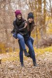Two girls having fun in autumn park stock photo
