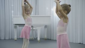 Two girls are having fun in ballet studio indoor. They talk friendly and turn bodies, raising their hands up. Adorable children dressed in classical dance stock footage