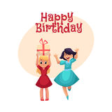 Two girls having fun at birthday party, dancing, holding gift Royalty Free Stock Images