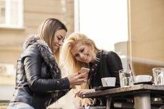 Two girls having fun while drinking coffee Stock Photos