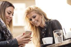 Two girls having fun while drinking coffee. Two beautiful girls having fun at a coffee shop Royalty Free Stock Photos