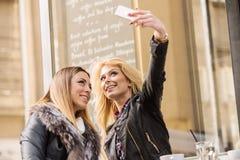 Two girls having fun while drinking coffee. Two beautiful girls having fun at a coffee shop Royalty Free Stock Image