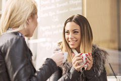 Two girls having fun while drinking coffee Royalty Free Stock Photos