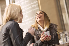 Two girls having fun while drinking coffee Royalty Free Stock Photography