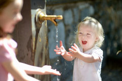Two girls having fun with drinking water fountain Royalty Free Stock Photos