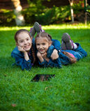Two girls having fun on grass with tablet Stock Photos