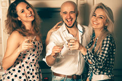 Two girls having fun with a guy at a party with a glass of marti Stock Image