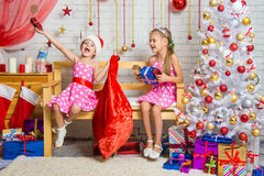Two girls having fun and happy New Year gifts from Santa Claus bag Royalty Free Stock Photos