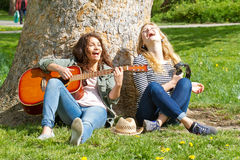 Two girls having fun with her instruments. Two girls in a park playing her instruments and singing a song Stock Photo