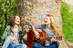 Two girls having fun with her instruments. Two girls in a park playing her instruments and singing a song Stock Image