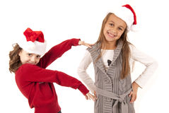 Two girls having fun playing around in santa hats Royalty Free Stock Photo
