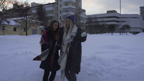 Two girls having fun and playing with snow outdoors in winter stock footage