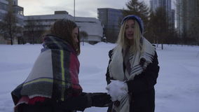 Two girls having fun and playing with snow outdoors in winter stock video footage