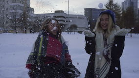 Two girls having fun and playing with snow outdoors in winter stock video