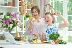 Two girls having fun while preparing fresh salad stock photo