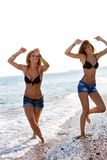 Two girls having fun at seaside. Royalty Free Stock Photos