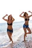 Two girls having fun at seaside. Royalty Free Stock Photos
