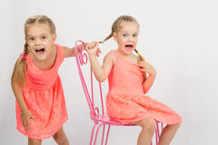 Two girls having fun and shout. Two girls sisters in the same clothes having fun playing with each other Royalty Free Stock Photo