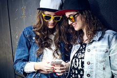 Two girls having fun with smartphones Royalty Free Stock Photography