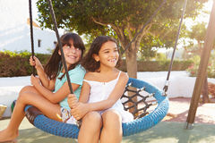 Two Girls Having Fun On Swing In Playground Stock Photo