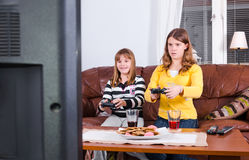Two girls having fun under playing games Stock Images
