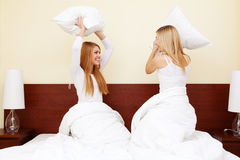 Two girls having a pillow fight in bedroom Stock Photos
