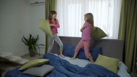 Two girls having pillow fight. Happy friends having fun together. friendly match stock video