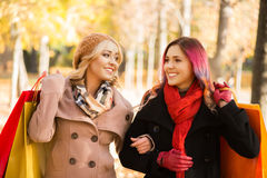 Two girls having a pleasant talk while walking the autumn park Royalty Free Stock Images