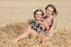 Two girls on hayloft Stock Images