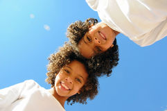 Two girls head to head. Two happy African American girls head to head against the blue sky Stock Images