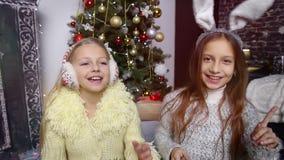 Two Girls in headphones listening music. Chirstmas. Two Girls in headphones listening music stock video footage
