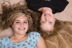 Two girls with heads together. Two teenage girls laying together with their heads together smiling Royalty Free Stock Image