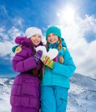 Two girls with heart made of snow Royalty Free Stock Photography
