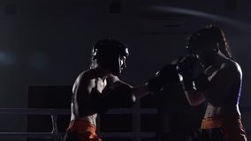 Two girls in helmets box their arms and legs in the ring in the dark. Slow motion