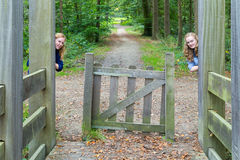 Two girls hiding at entry in nature Stock Images