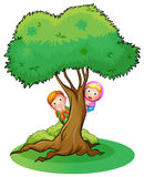 Two girls hiding at the tree Stock Image