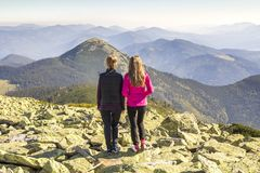 Two girls hikers standing in mountains enjoying mountain view Stock Images