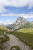 Two girls hiking with the Midi d'Ossau peak Stock Photos