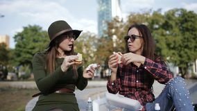 Two girls hipster eating sandwiches in the Park, laugh and talk. Stay in the Park. The holiday sandwich. Urban picnic in the Park. Two girls hipster talk and stock footage