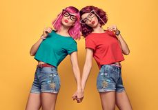 Two Girls Hipster Friends Having Fun with Props. Two Girls Hipster Friends Crazy with Props. Fashion. Happy Young Pretty Woman Blowing lips. Playful Cool Model Stock Photography