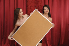 Two girls hold empty board Royalty Free Stock Photos