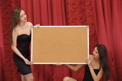 Two girls hold empty board Stock Photo