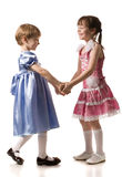 Two girls hold hands of each other Stock Photos