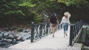 Two girls hold hands and fun run across the bridge over a clean fast river, blonde and brunette with flying long hair stock video footage