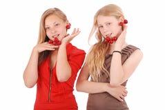Two girls hold in lips fresh cherries Stock Photo