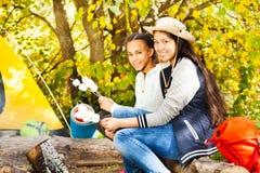 Two girls hold marshmallow sticks near bonfire Royalty Free Stock Photography