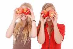 Two girls hold near eyes fresh apples Royalty Free Stock Photography