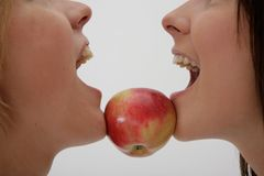 Two girls holding apple between chins Stock Images
