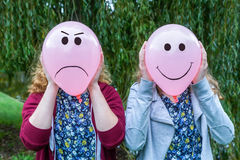 Two girls holding balloons with facial expressions Royalty Free Stock Image