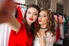 Two girls holding camera and taking self portrait at store. stock photography
